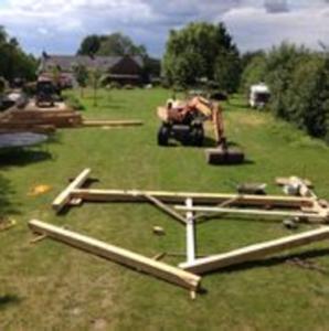 afbeelding: grasveld met houten diverse houten balken voor spantconstructie en graafmasschine