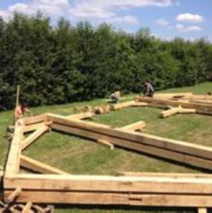 afbeelding: houten dakconstructie liggend op grasveld met bouwvakkers