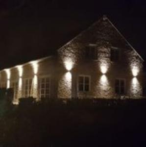 afbeelding: foto boerderij in avond met sfeerverlichting aan gevel