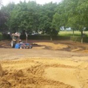 afbeelding: tractor met bomen en zandvlakte